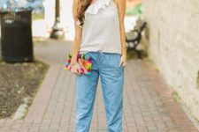 With white ruffled one shoulder blouse, colorful clutch and beige high heels