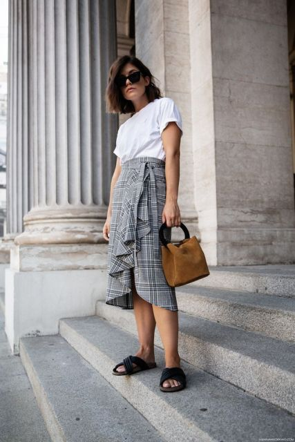 With white t shirt, brown suede bag and black flat mules