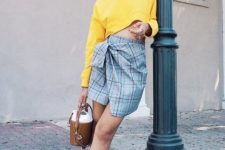 With yellow cropped shirt, brown mini bag and yellow mules