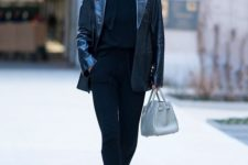 Yolanda Hadid wearing a black hoodie, black pants, booties, a black lacquer leather blazer and carrying a blue bag