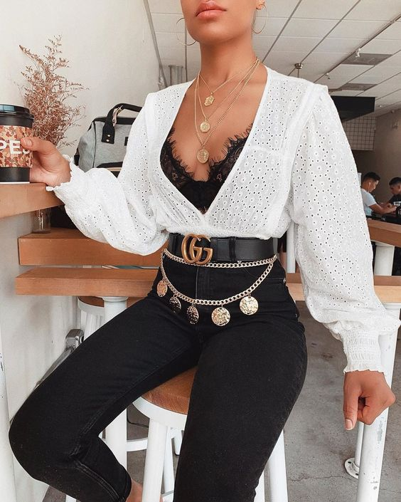 a black lace bra, a white perforated shirt, black skinnies, a gold chain belt with pendants