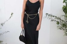 a black slip midi dress, a gold chain belt, a black bag and acrylic shoes for a special occasion