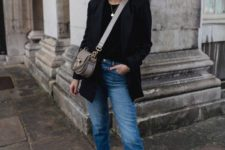 a black top, a black blazer, blue jeans, black square top booties and a small grey bag for spring