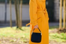 a bold spring look in black and sunny yellow, with a black turtleneck, a black bag, black platform shoes and a sunny yellow trench