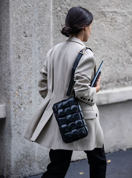 a chic black woven leather bag worn on one shoulder is a trendy statement in your look