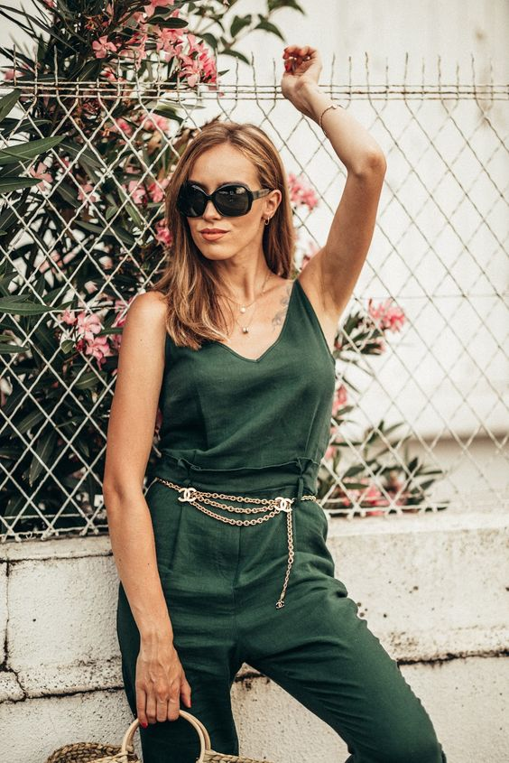 a green jumpsuit, a copper chain belt, a wicker bag and floral sneakers for a spring to summer look