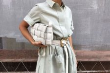 a light green midi dress with pockets, a white belt, a white woven clutch for an ultimate modern look