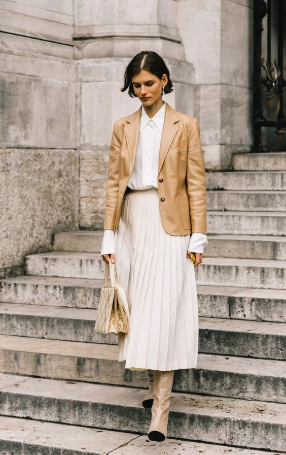 a modest spring work look with a white shirt, a neutral pleated midi, neutral boots, a tan leather blaer and a snakeskin bag