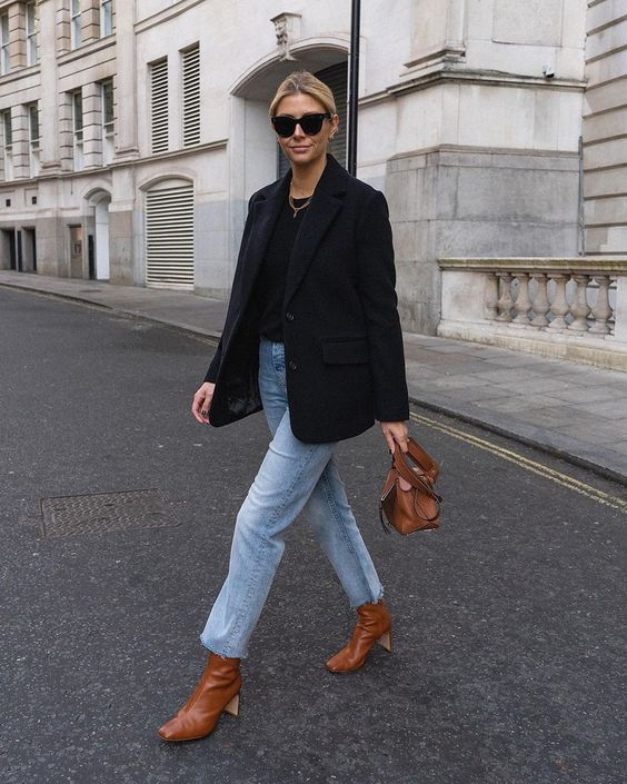 a navy oversized blaer, a black tee, light blue jeans, brown square toe booties and a brown bag