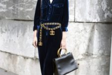 a navy velvet jumpsuit in 70s style, a chunky chain belt with logos, pink shoes and a black bag for a bold work look