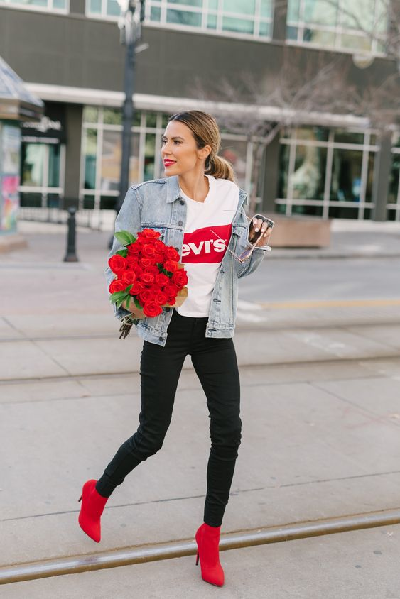 a printed tee, black skinnies, red booties, a washed out oversized denim jacket for a casual look