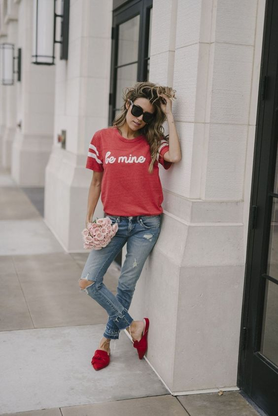 a red printed tee, blue ripped jeans, red suede slipper mules for a casual sporty look