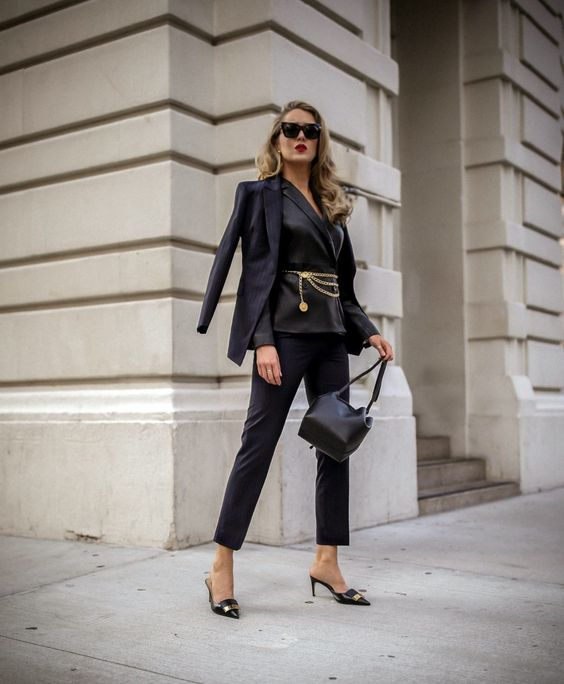 a refined look with a black pantsuit, a gold chain belt, a second blazer, a black bag and mules for a special occasion