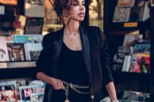 a refined outfit with a black top, pants, a tux blazer, a silver bag and a chunky chain belt plus a pendant and statement earrings