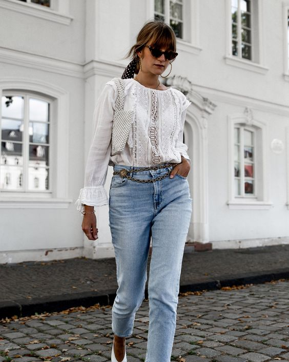 a romantic look with a white Victorian shirt, blue jeans, a vintage chain belt and a pearly bag