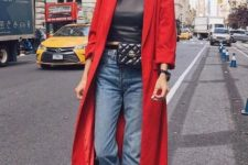 a simple red trench worn with two tone jeans, white booties, a waist bag and a black leather top