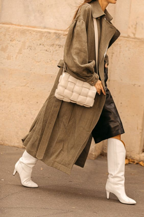 a spring look with a black skirt, white wide knee boots, a grey trench and a white woven leather bag