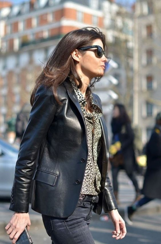 a trendy 90s inspired look with an animal print shirt, a black leather blazer and black jeans