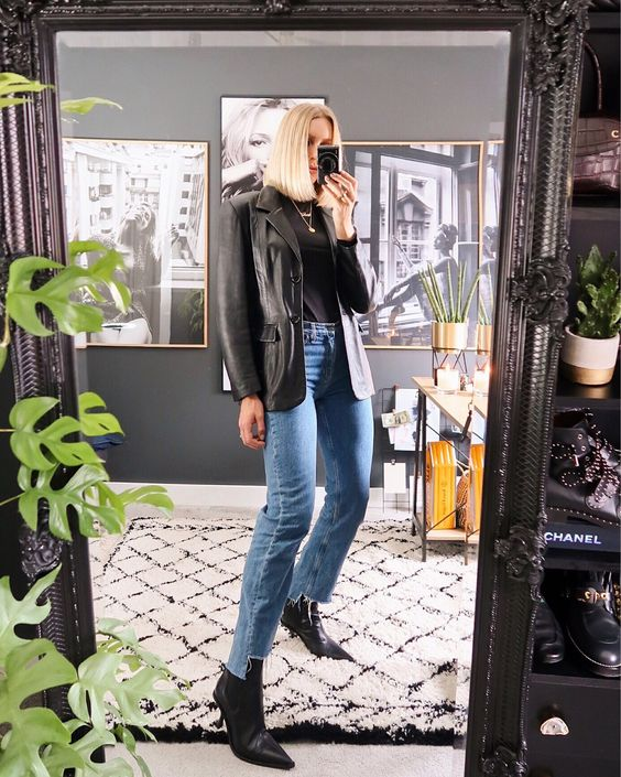 a trendy look with a black tee, a black leather blazer, blue jeans, black booties for spring