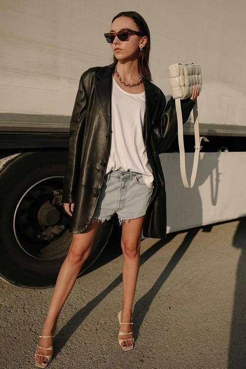 a trendy look with a white tee, denim shorts, nude strappy sandals and a black leather blazer plus a woven bag