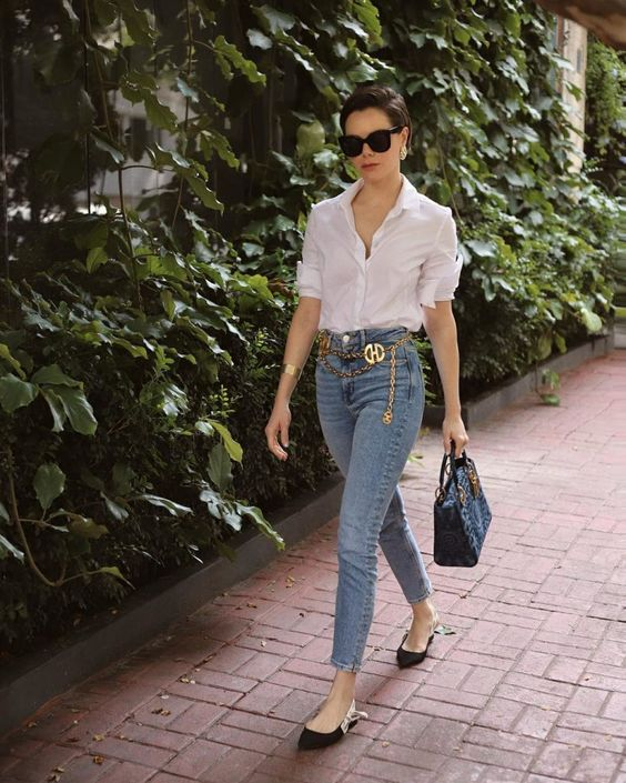 a white shirt, light blue cropped skinnies, black flats and a black bag plus a gold chain belt with a logo