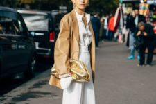a white shirt, white culottes, white square toe shoes, a camel oversized leather jacket and a gold shiny clutch