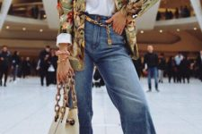 a white tee, blue jeans with ripped hems, a gold chain belt, a floral blazer, white shoes and a white bag on chains