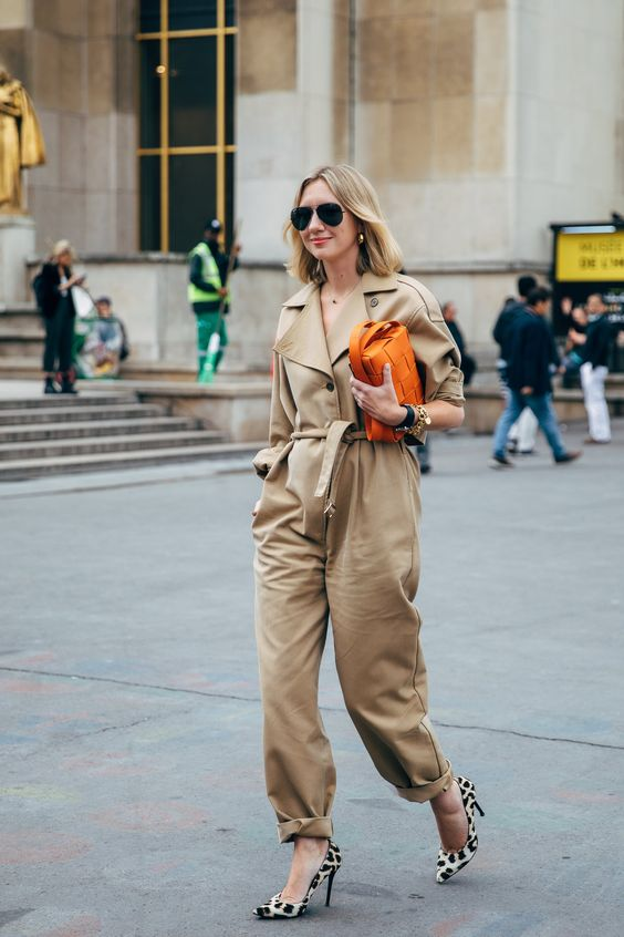 an oversized tan jumpsuit with a sash, leopard print shoes, an orange woven leather clutch for a bright touch