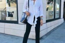 black straight jeans, a white oversized shirt, a clear bag and bold blue square toe heels