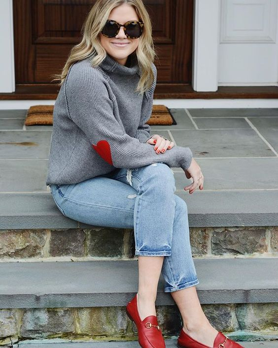blue ripped straight jeans, red moccasins, a grey turtleneck sweater with hearts on elbows