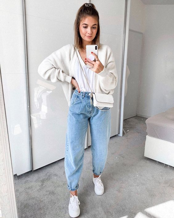 a casual outfit with a white top, blue slouchy jeans, white sneakers, a cardgian and a crossbody bag