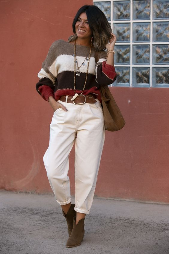 a boho look with white slouchy jeans, brown booties, a striped oversized sweater, a brown bag