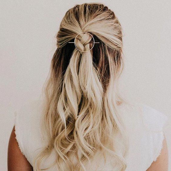 a wavy half updo with a braided element and waves down plus an orbital hair pin is a trendy idea