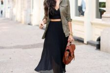 05 a black crop top, a black midi skirt, brown strappy shoes, a brown backpack and a green cargo jacket