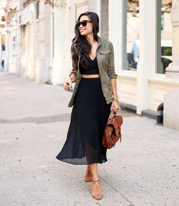 a black crop top, a black midi skirt, brown strappy shoes, a brown backpack and a green cargo jacket