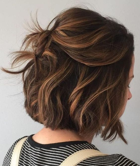 a messy half updo with a bump on top and some waves lets you swipe your hair off the face