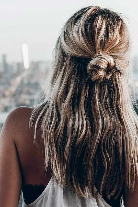 a messy half updo with a twisted bun and textural locks is what you can eaisly make right now
