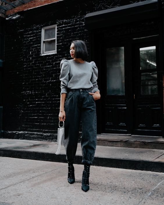 a spring look with a grey top with puff sleeves, black slouchy jeans, black booties with spikes and a grey bag