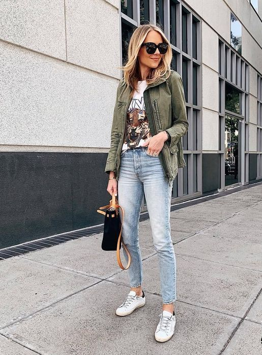 a printed tee, an olive green cargo jacket, light blue jeans, white sneakers and a black bag