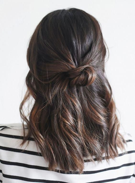 a simple wavy half upfo with a messy knot and some locks down is a cool idea for medium hair