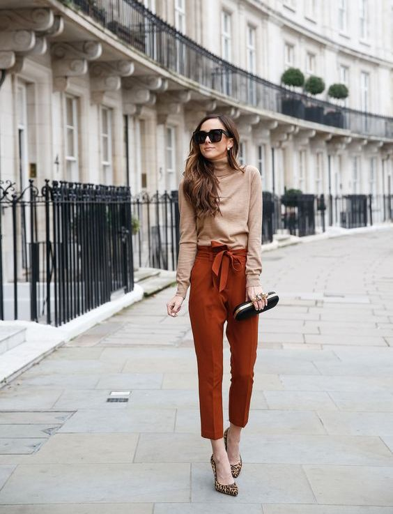 a fall look with a tan turtleneck, rust colored cropped pants, animal print shoes and a black clutch