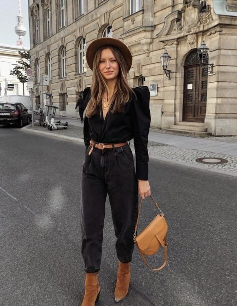 a statement and fashionable look with a black blouse with catchy shoulders, black slouchy jeans, brown booties and a hat plus a saddle bag