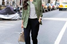 11 a striped tee, black pants, an olive green cargo jacket, tan laser cut shoes and a tan bag