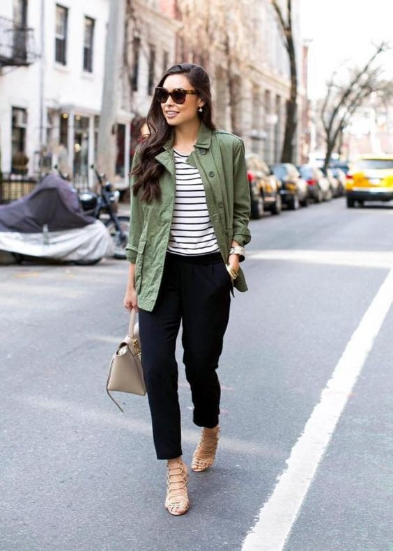 a striped tee, black pants, an olive green cargo jacket, tan laser cut shoes and a tan bag