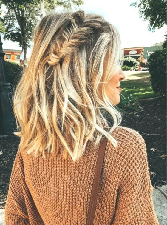 a wavy half updo with a large fishtail braid on top and textural hair for a cool and chic look