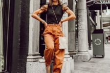 12 a bold outfit with a black top with sheer sleeves, rust slouchy pants, nude booties and a silver sequin bag