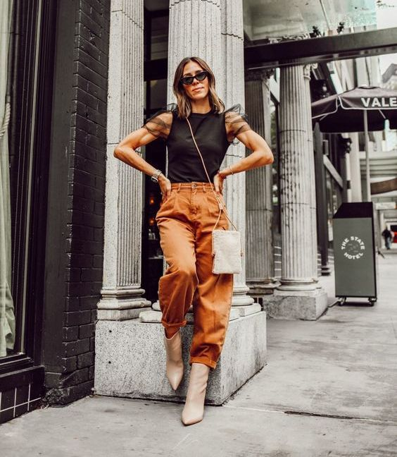 a bold outfit with a black top with sheer sleeves, rust slouchy pants, nude booties and a silver sequin bag