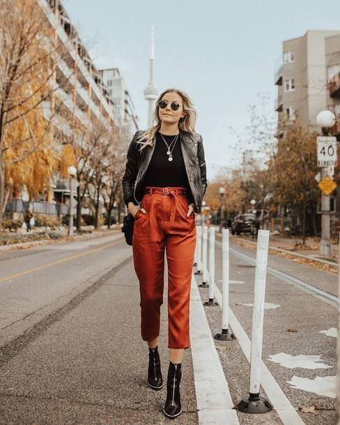 a fall outfit with a black top, rust cropped pants, black boots, a black leather jacket