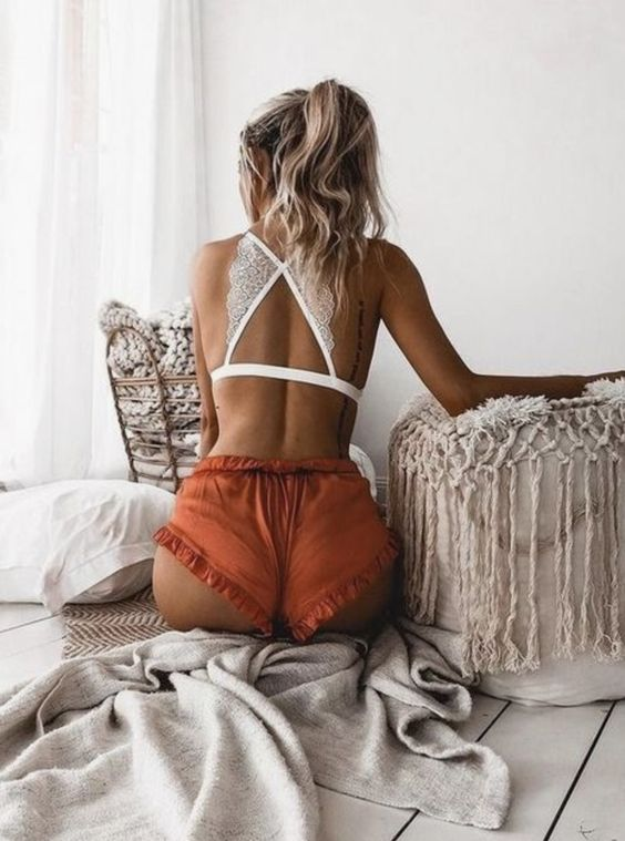 a white lace crop top with a criss cross back and rust colored ruffle mini shorts are a bold combo