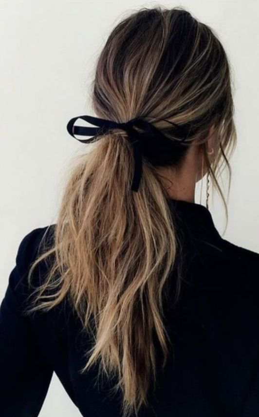 a low messy ponytail with textural hair down and a ribbon is a timeless idea that works for every type of hair